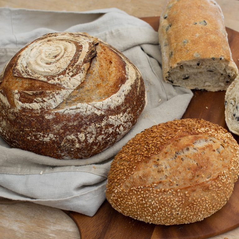 "alt=""Wholesale bread supply of rustic bread consisting round sourdough, sesame bread and olive bread baked by sourdough factory for restaurants"""